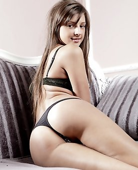 Adorable dark haired shapely chick in sexy lingerie showing cute shaved cunt on the sofa.